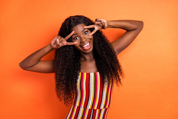 Photo of dark skin happy nice cheerful woman hold hands face v-signs isolated on orange color...