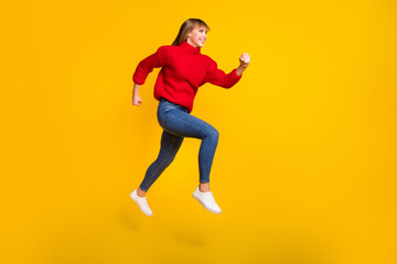 Wall Mural - Full size profile photo of blond optimistic lady jump wear red sweater jeans sneakers isolated on bright yellow color background