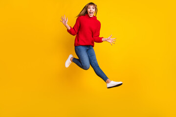 Wall Mural - Full size profile photo of blond optimistic lady jump yell wear red sweater jeans sneakers isolated on bright yellow color background