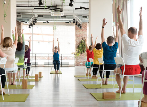 group of senior people doing yoga with chairs and with attractive young male teacher indoor