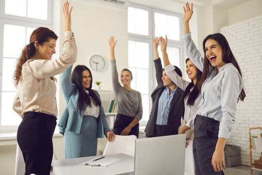 Team of happy women raising hands, supporting good suggestion and voting for idea of making changes in corporate group meeting or in motivational mentoring session with online business growth coach
