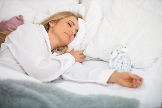 Blonde adult woman in white shirt sleeping