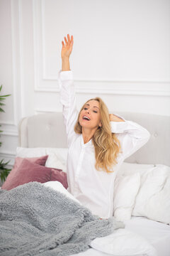 Waking up joyful woman at home in bed