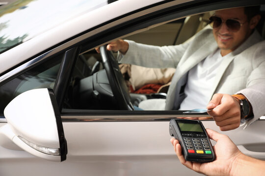Man sitting in car and paying with credit card at gas station, focus on hand