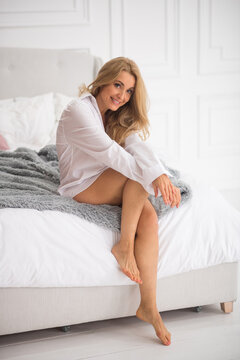 Woman with bare feet sitting on bed.