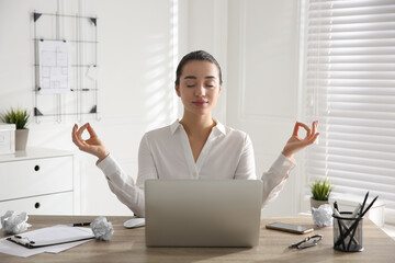 Fototapeta Young businesswoman meditating at workplace. Stress relief exercise obraz