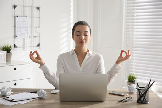 Young businesswoman meditating at workplace. Stress relief exercise
