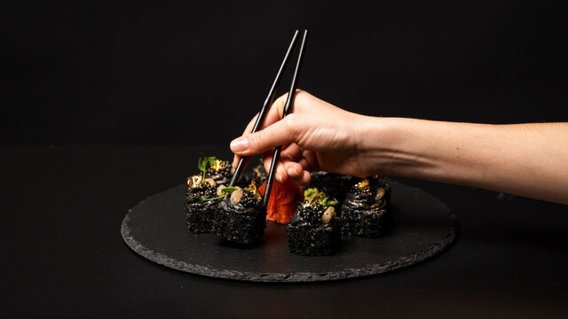 Hand with chopsticks wants to take custom sushi roll with black rice, crab meat, avocado, smoked salmon mousse, oar caviar, masago, shrimp cocktail, edible gold leaf, ginger, wasabi on black table.