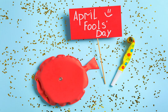 Sign with phrase April Fools' Day, whoopee cushion and party blower on light blue background, flat lay