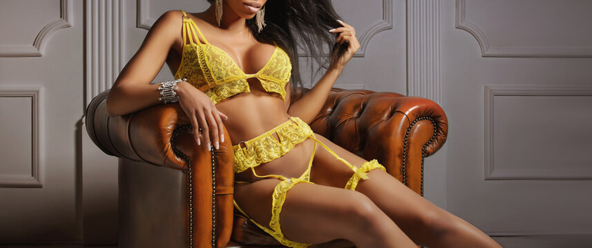 Sexy young woman with long legs sitting on a dark brown leather armchair