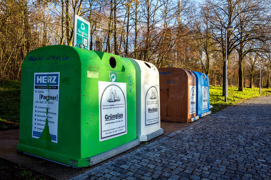 Berlin, Germany - November 15, 2017: Set of different color recycle garbage bins near car highway, waste separation concept.
