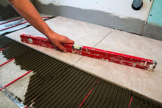 Ceramic tiles and tools for tiler. Worker hand installing floor tiles. Home improvement, renovation - ceramic tile floor adhesive, mortar, level.