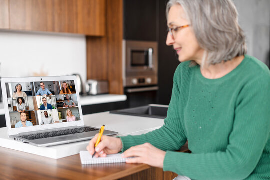 A senior mature gray-haired lady sits at the kitchen desk at home studying online on a laptop, watching a webinar with diverse group, participating in the online conference, taking a notes. Video call