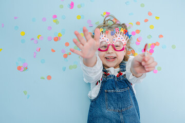 Little girl in happy birthday glasses jeans overalls lies on a blue-surfaced floor with colorful...