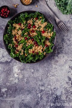 Healthy raw kale and quinoa salad with cranberry and pine nut.
