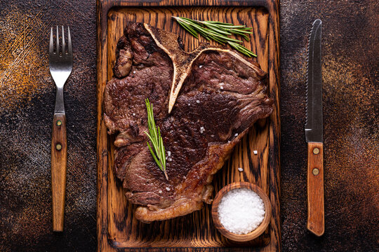 Grilled beef steak with spices on a wooden board