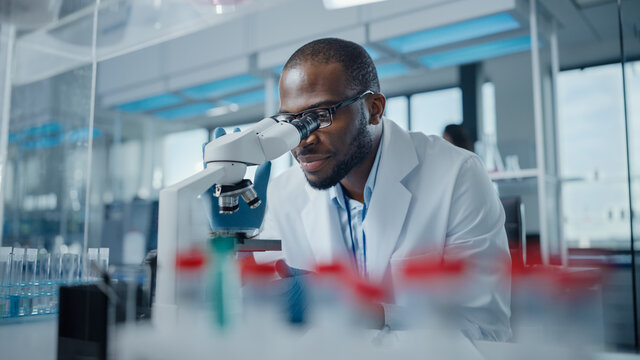 Modern Medical Research Laboratory: Portrait of Male Scientist Looking Under Microscope, Analysing Samples. Advanced Scientific Lab for Medicine, Biotechnology, Microbiology Development