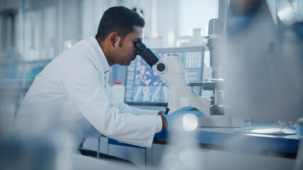 Medical Research Laboratory: Male Scientist Looking Under Micrsocope, Analyzing Samples. Advanced...
