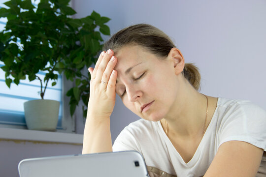 young woman looks at a smartphone and holds her head with her hand, the concept of a headache or disorder, depression
