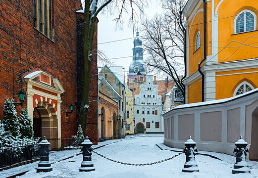 Old European town square and snow-covered narrow street in winter time