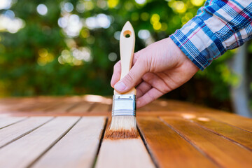 a hand holding a brush applying varnish paint on a wooden garden table - painting and caring for...