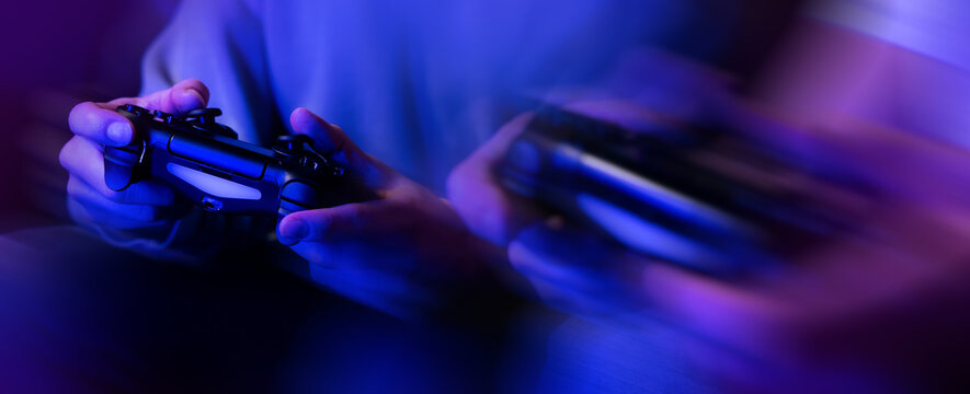 gamers playing console video games. controller in hands closeup. neon lights banner