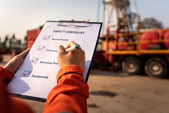 Action of safety office is writing on checklist paper during safety audit and risk verification at drilling site operation with blurred background of mount truck rig. Selective focus at hand.