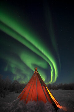 A swirling Aurora Borealis (Northern Lights) over a traditional Sami teepee in Northern Sweden, Scandinavia, Europe