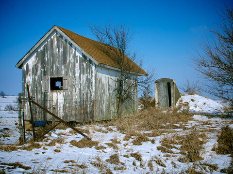 A winter scene of a rural  abandoned shed and storm cellar next to a fence in the snow, near Loeffler, Missouri, 2008