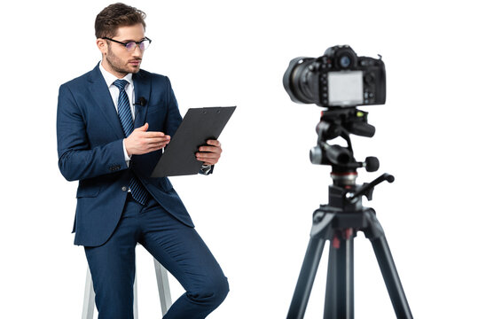 news anchor pointing at clipboard while sitting on high stool near digital camera on blurred foreground isolated on white