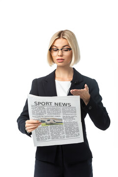 blonde broadcaster in eyeglasses pointing with hand at sport news newspaper isolated on white