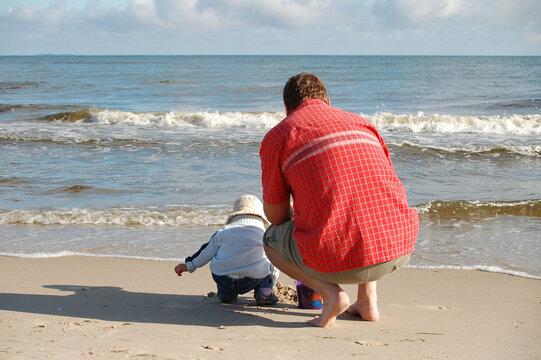 Familie mit Kleinkind am Sandstrand spielend