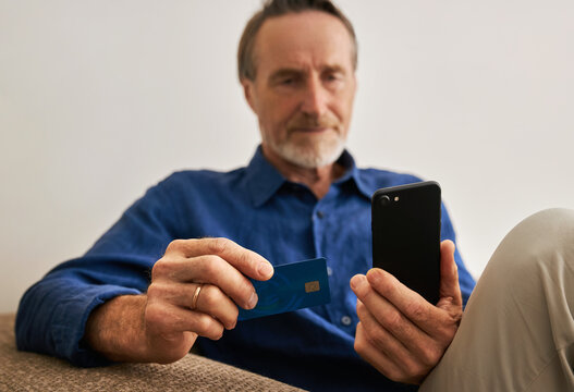 Close up of hands of a senior man holding a smartphone and credit card while sitting on a couch
