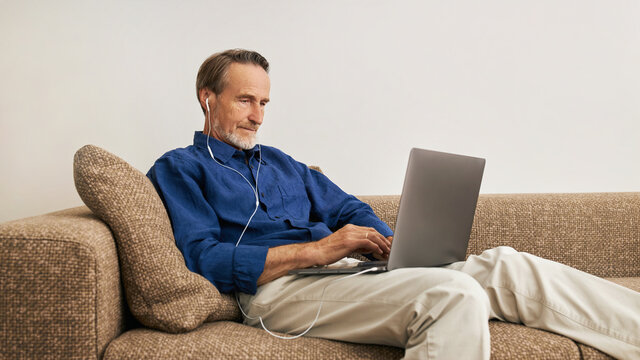 Senior man lying on a couch in the living room with a laptop on his hips