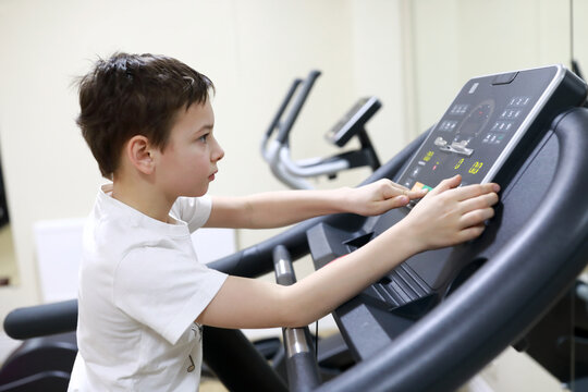 Boy exercising at stride treadmill