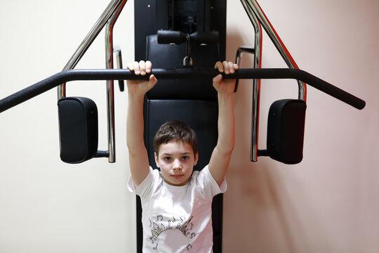 Child doing exercises for back load on simulator