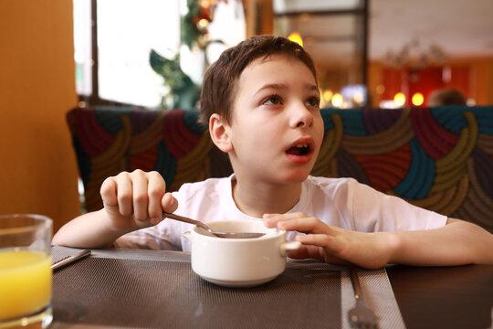 Boy has breakfast in restaurant