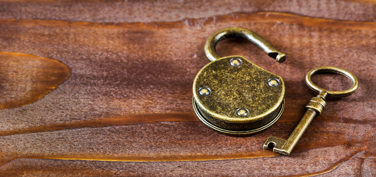 Escape room game concept, old vintage golden key and padlock. Web banner with copy space.