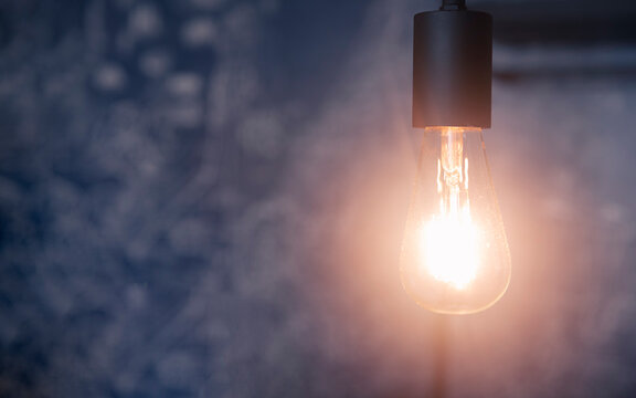 Retro light bulb on the ceiling with blue background and copy space