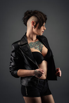 Attractive tattooed young woman, in profile, with a punk hairstyle, wearing a bra, leather jacket and fishnet stockings
