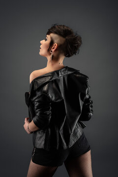 Pretty young woman from back with punk hairstyle, showing off her shoulder, wearing leather jacket and fishnet stockings