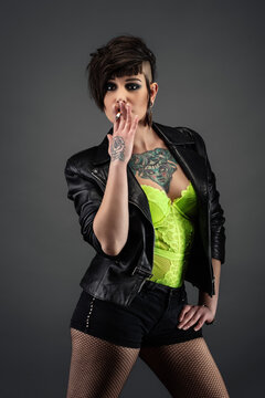 Attractive tattooed young woman, full face, with punk hairstyle, wearing leather jacket, yellow lace bodysuit, fishnet stockings, holding cirarette in her hand