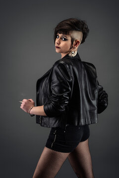 Attractive young woman from back, with punk hairstyle, wearing leather jacket, fishnet stockings, holding cirarette in her hand