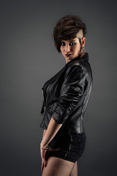 Attractive young woman from profile, with punk hairstyle, wearing leather jacket and fishnet stockings