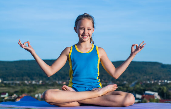 happy kid in sport training clothes workout in meditation yoga pose, harmony