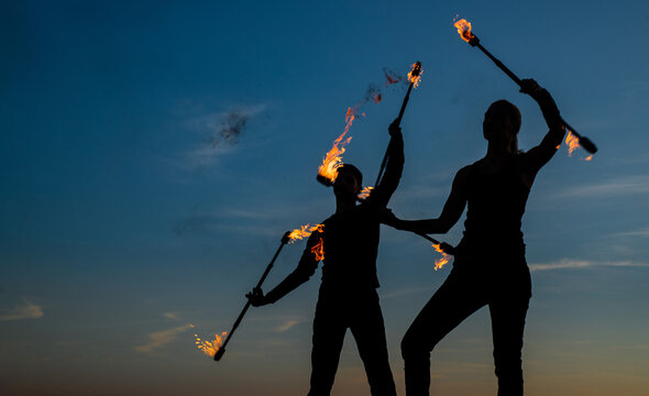 Couple of man and woman perform flaming baton twirling during fire performance in dark silhouettes on idyllic evening sky outdoors, coordination