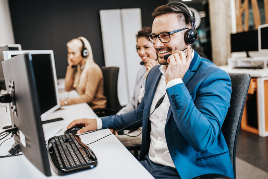 Handsome male customer service agent with headset working in call center.