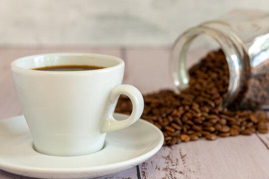 Frasco de vidrio con semillas de cafe  tostado desparramadas sobre una mesa, acompañando a una taza de cafe