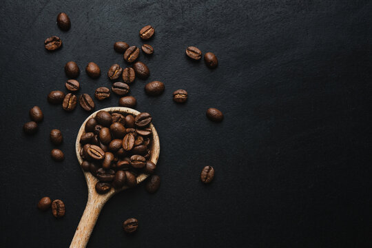 Coffee beans in spoon on dark