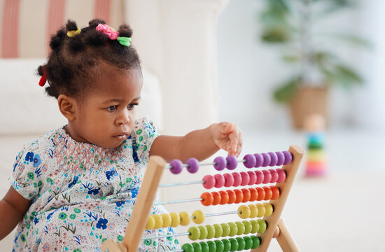 cute african american baby girl playing colorful abacus toy at home